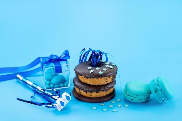 Donuts van een vooraanzichtchocolade samen met blauwe, franse macarons en suikergoed op blauw, het koekjeskleur van de suikergoed zoete cake