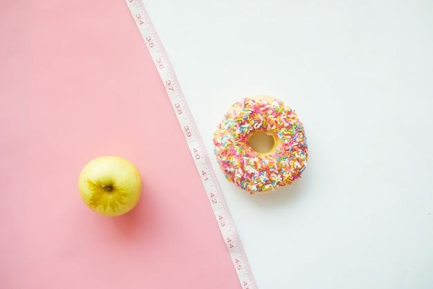 Donuts vergelijken met groene appel op kleuroppervlak