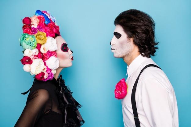 Dood huwelijk. profielfoto van eng paar man bruid dame dichtbij stuur lucht kusjes sluit ogen draag zwarte jurk dood kostuum rozen hoofdband bretels geïsoleerde blauwe kleur achtergrond