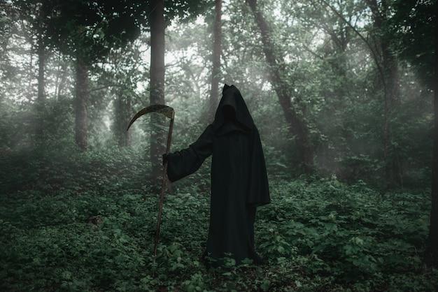 Dood in een zwarte hoodie met een zeis in het bos