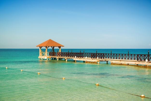 Dood kalm. houten pier, turquoise zee, blauwe horizon en heldere wolkenloze hemel.