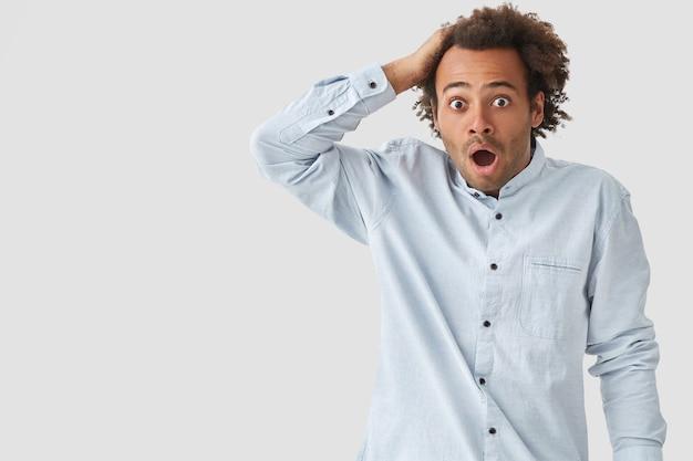 Doodsbang man van gemengd ras met knapperig haar, opent mond wijd, heeft angstige uitdrukking, gekleed in wit overhemd, poseert voor muur