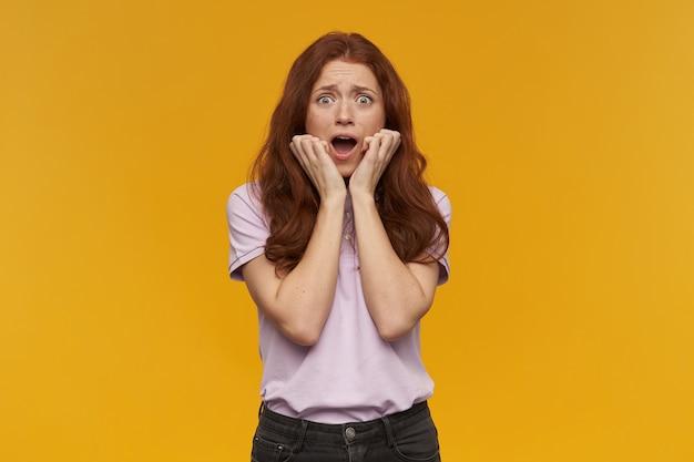 Doodsbang meisje, bange roodharige vrouw met lang haar. roze t-shirt dragen. mensen en emotie concept. haar gezicht aanraken. bevroor van afgrijzen. geïsoleerd over oranje muur