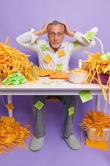 Doodsbang multitasking oudere man kijkt met paniek houdt handen op het hoofd kan niet beslissen wat eerst te doen in verlegenheid gebracht door deadline poses in coworking space draagt formele kleding