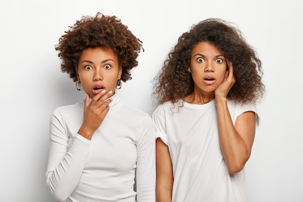 Doodsbang twee zussen met afro-kapsel, verbijsterd voelen, horrorfilm kijken, witte vrijetijdskleding dragen, onrustig zijn, binnen staan, geïsoleerd op witte achtergrond.