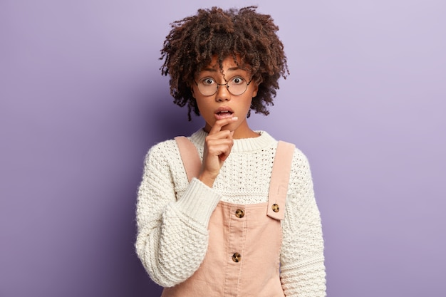 Doodsbange jonge vrouw met donkere huid en afro-kapsel, heeft ingehouden adem, ziet er verrassend uit, hoort schokkend nieuws
