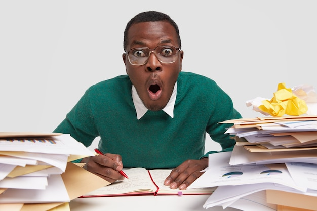 Doodsbange man met donkere huid schrijft informatie in organizer, draagt grote bril, heeft rotzooi aan bureau, stapels proppen papier