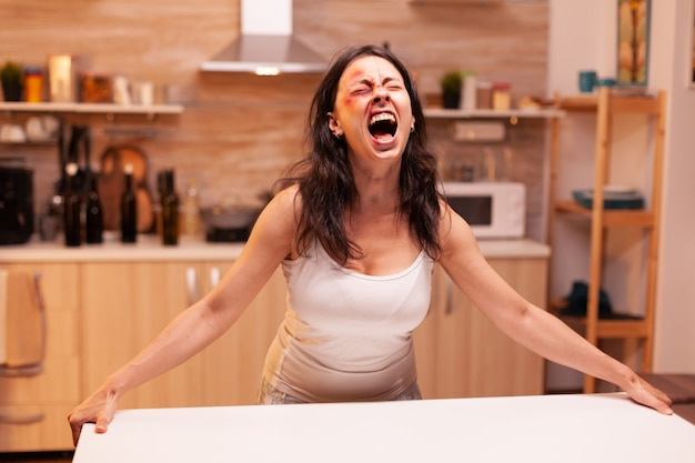 Doodsbange vrouw die schreeuwt nadat ze op brute wijze is geslagen door een alcoholische echtgenoot. gewelddadige agressieve echtgenoot die de doodsbange hulpeloze, kwetsbare, bange, geslagen en paniekerige vrouw verwondt.