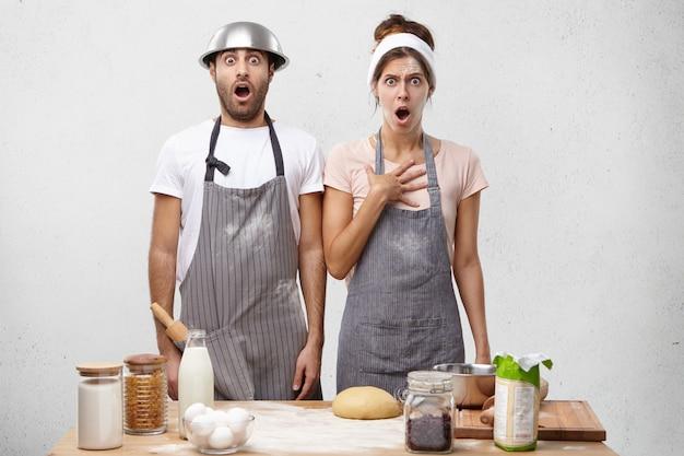 Doodsbange vrouwelijke en mannelijke koks kijken met wijd geopende mond naar de keuken