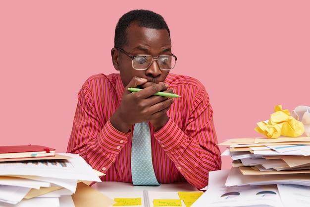 Doodsbange zwarte directeur bedekt mond met beide handen, staart naar grafieken, realiseert zijn faillissement, houdt pen vast, heeft veel papierwerk