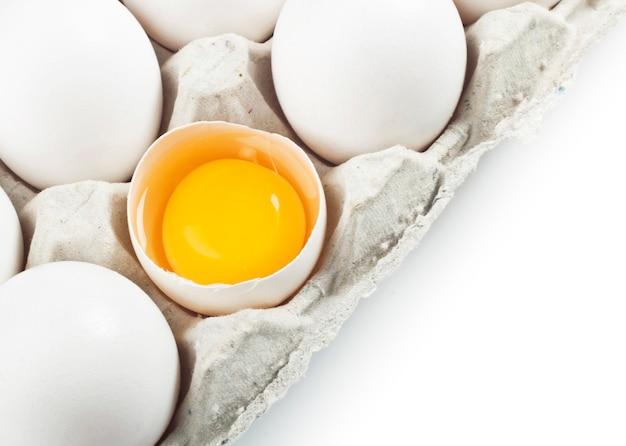 Dooier in een eierschaal met witte eieren in een doos