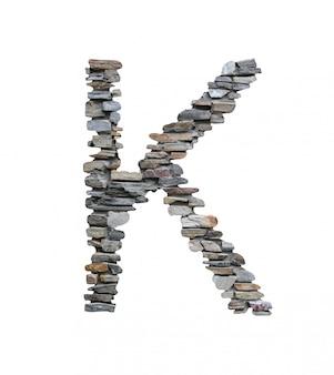 Doopvont van k om van steenmuur te creëren die op wit wordt geïsoleerd.
