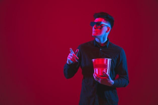 Door een 3d-bril kijken. portret van een blanke jongeman geïsoleerd op rode muur in neonlicht. mooi modelletje. concept van menselijke emoties, gezichtsuitdrukking, jeugd, apparaten.