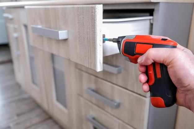 Door elementen van keukenmeubilair in vintage stijl te monteren, draait de meester de schroef met een elektrische schroevendraaier