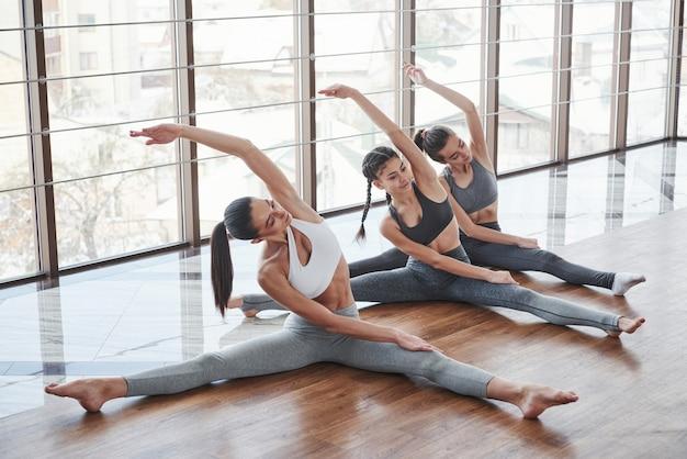 Door het glas zie je de gebouwen. drie meisjes heeft fitness dag in de kamer met houten vloer en grote ramen