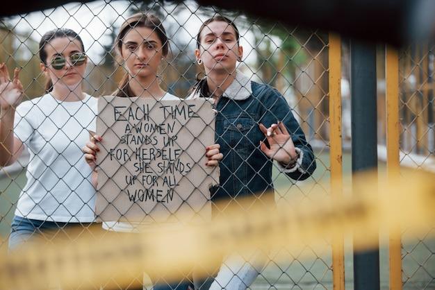 Door het hek. een groep feministische vrouwen protesteert buitenshuis voor hun rechten