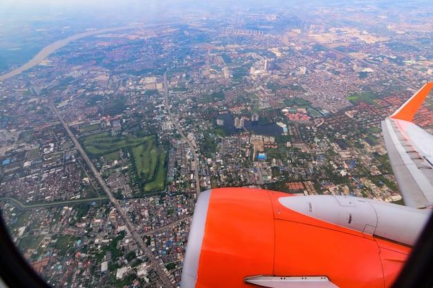 Door vliegtuigraam kijken en overzichtsstad zien.
