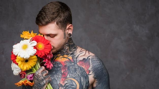 Doorboorde jonge mens met tatoegering op zijn lichaam die de mooie gerberabloem ruiken