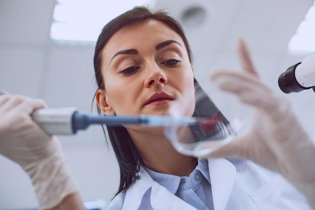 Doorbraak. bekwame slimme wetenschapper die een bloedtest uitvoert en een uniform draagt