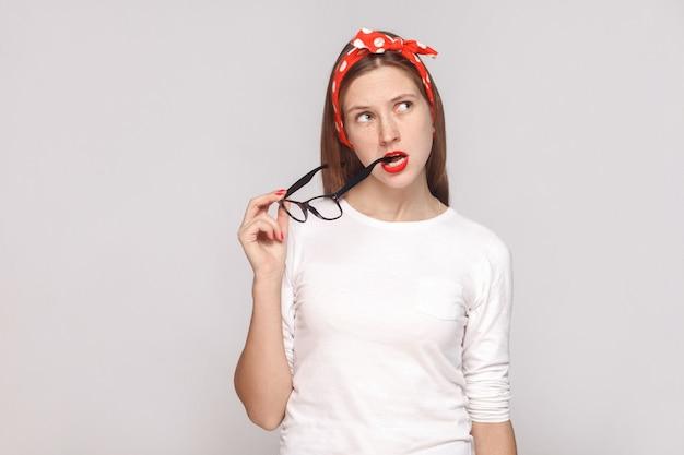 Doordacht portret van mooie emotionele jonge vrouw in wit t-shirt met sproeten, zwarte bril in haar mond, rode lippen en hoofdband. indoor studio opname, geïsoleerd op lichtgrijze achtergrond.