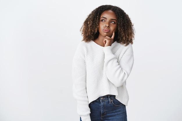 Doordachte aantrekkelijke jonge afro-amerikaanse vrouw met krullend haar in trui die beslist welke kleding over een witte muur staat, loensend als denkend, wang aanrakend