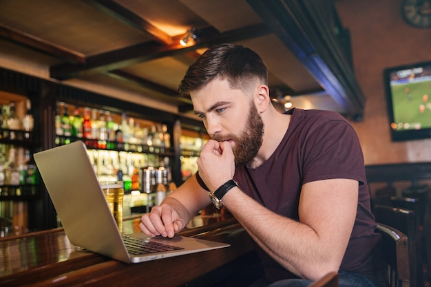 Doordachte aantrekkelijke jonge man zit en gebruikt laptop in bar in