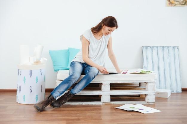 Doordachte aantrekkelijke jonge vrouw schilder zittend en met behulp van tablet in werkplaats