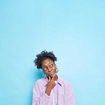 Doordachte afro-amerikaanse vrouw houdt haar kin vast en kijkt naar boven, waardoor de beslissing overdenkt