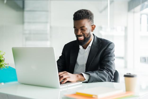 Doordachte afro-amerikaanse zakenman met behulp van laptop, nadenken over project, bedrijfsstrategie, verbaasd werknemer executive kijken naar laptop scherm, e-mail lezen, besluit nemen op kantoor