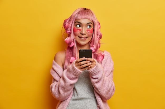 Doordachte aziatische vrouw krijgt haar gestileerd, krulspelden, schoonheid collageen patches van toepassing, mobiele telefoon in handen houdt