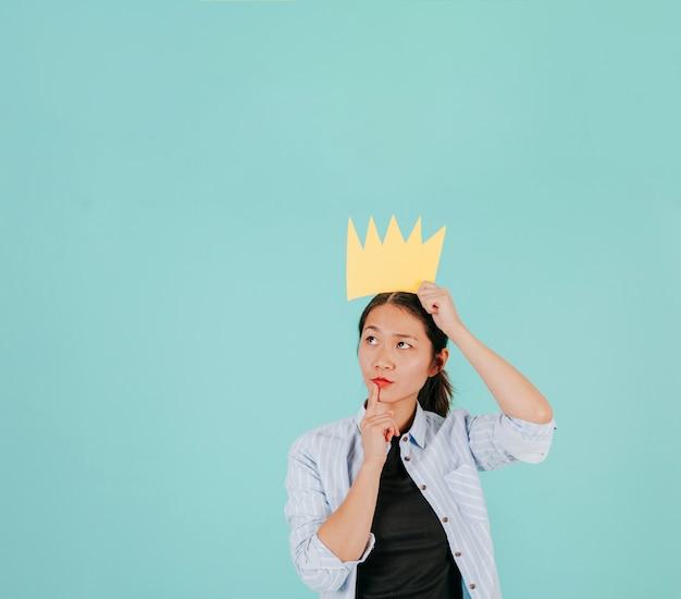 Doordachte aziatische vrouw met papieren kroon
