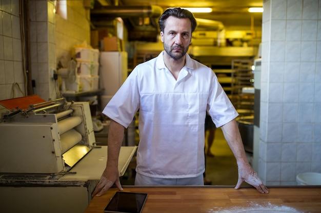 Doordachte bakker die zich bij het werk toonbank