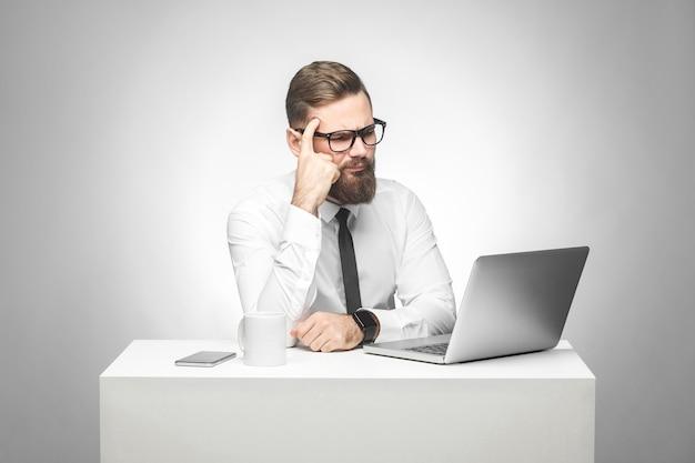 Doordachte, bebaarde jonge baas in wit overhemd en zwarte stropdas zit op kantoor op het bureau en kijkt naar het dagelijkse rapport op de laptop, heeft een nieuw idee en plant een eigen strategie, houdt een hand op het hoofd.