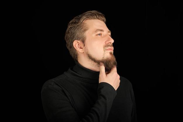 Doordachte bebaarde man, half profiel portret, zwarte achtergrond. jonge kerel in zwarte polohals trui. reflecterende en denkende succesvolle man.