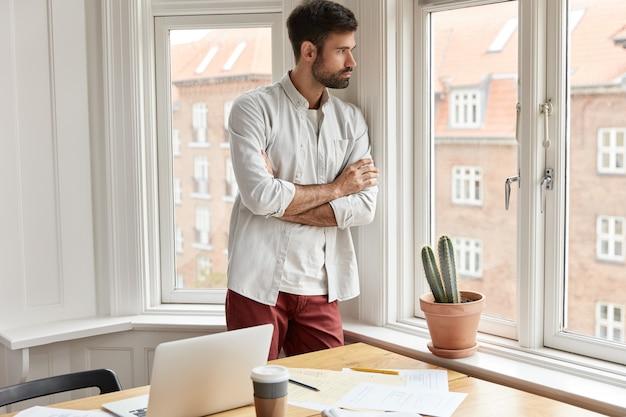 Doordachte bebaarde projectmanager thuis werken