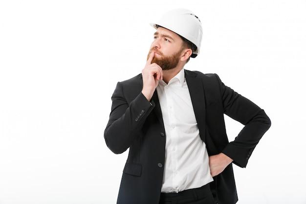 Doordachte bebaarde zakenman in beschermende helm wegkijken
