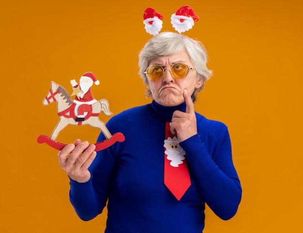 Doordachte bejaarde vrouw in zonnebril met santa hoofdband en santa stropdas legt vinger op kin en houdt santa op schommelpaard decoratie opzoeken geïsoleerd op een oranje achtergrond met kopie ruimte
