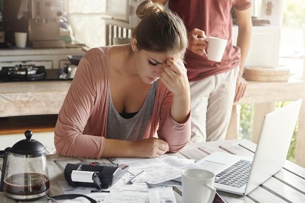 Doordachte beklemtoonde jonge vrouwelijke zittend aan de keukentafel met papieren en laptopcomputer probeert te werken door middel van stapel rekeningen, gefrustreerd door het bedrag van de binnenlandse uitgaven tijdens het doen van gezinsbudget