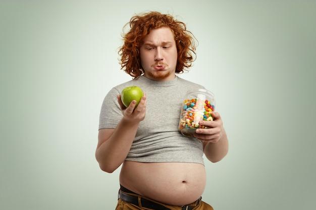 Doordachte besluiteloze roodharige dikke man met dikke buik, verward en aarzelend, voor moeilijke keuze: of hij nu gezonde biologische appel eet of ongezonde snoepjes