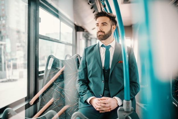 Doordachte blanke bebaarde zakenman in turquoise pak zitten in de openbare bus en op zoek via raam. grenzen bestaan alleen in de geest.