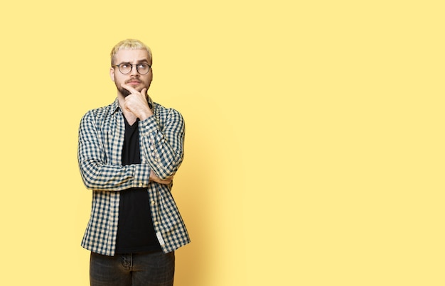 Doordachte blanke blonde man met baard raakt zijn kin aan en poseert op een gele muur met vrije ruimte