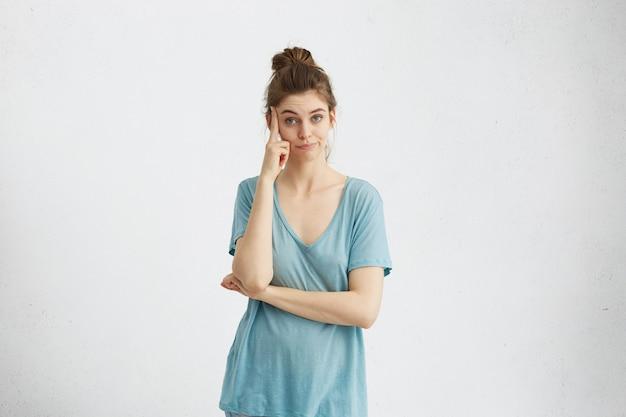 Doordachte blanke vrouw draagt een casual blauw t-shirt met vinger naar haar slaap, verward nadenkend kijken, nadenken, alle voor- en nadelen van het voorstel afwegen