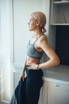 Doordachte blanke vrouw in sportkleding is poseren voordat ze afslankoefeningen doet tijdens de digitale fitness-sessie