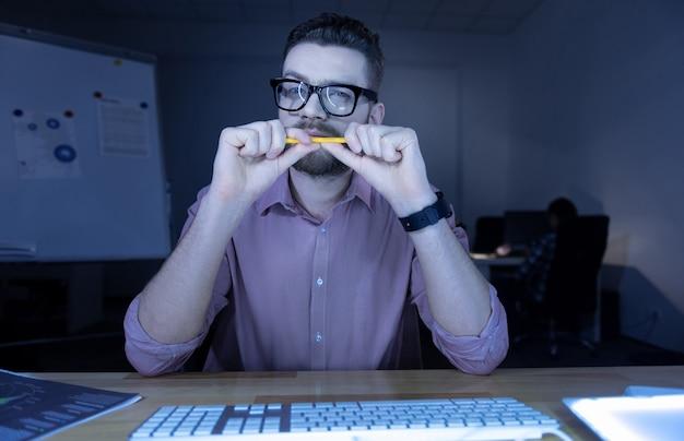 Doordachte blik. aardige, bebaarde, prettige man die voor het computerscherm zit en ernaar kijkt terwijl hij een potlood vasthoudt