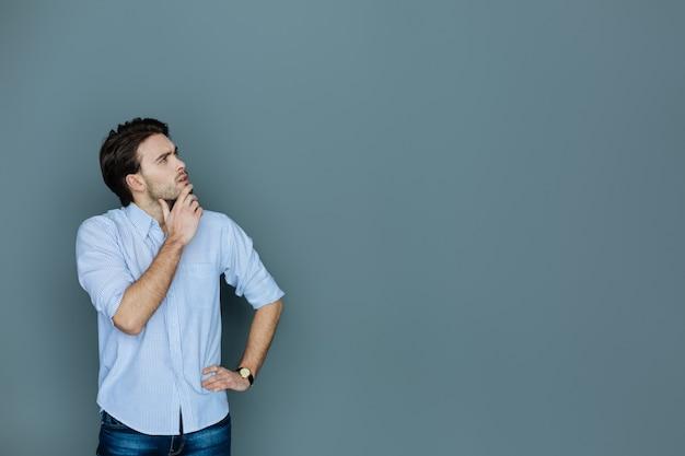 Doordachte blik. slimme knappe bedachtzame man die zijn kin vasthoudt en omhoog kijkt terwijl hij tegen de grijze achtergrond staat