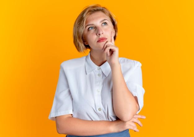 Doordachte blonde russische meisje legt hand op kin opzoeken geïsoleerd op een oranje achtergrond met kopie ruimte