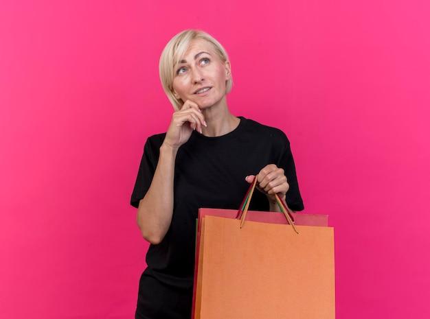 Doordachte blonde slavische vrouw van middelbare leeftijd met boodschappentassen kin aanraken opzoeken geïsoleerd op roze muur met kopie ruimte
