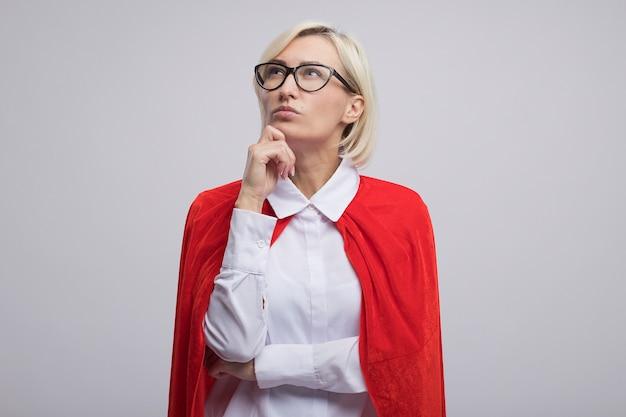 Doordachte blonde superheld vrouw van middelbare leeftijd in rode cape met een bril die de hand op de kin legt en omhoog kijkt