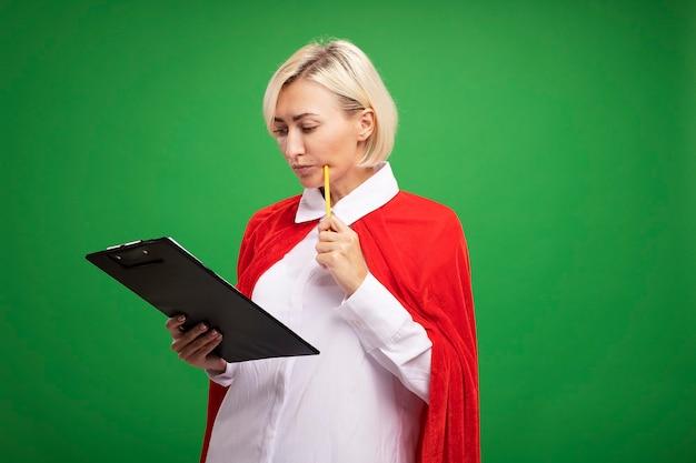Doordachte blonde superheldenvrouw van middelbare leeftijd in rode cape die klembord vasthoudt en de wang aanraakt met potlood