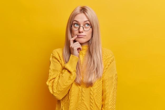 Doordachte blonde vrouw geconcentreerd boven diep in gedachten draagt casual trui met ronde bril